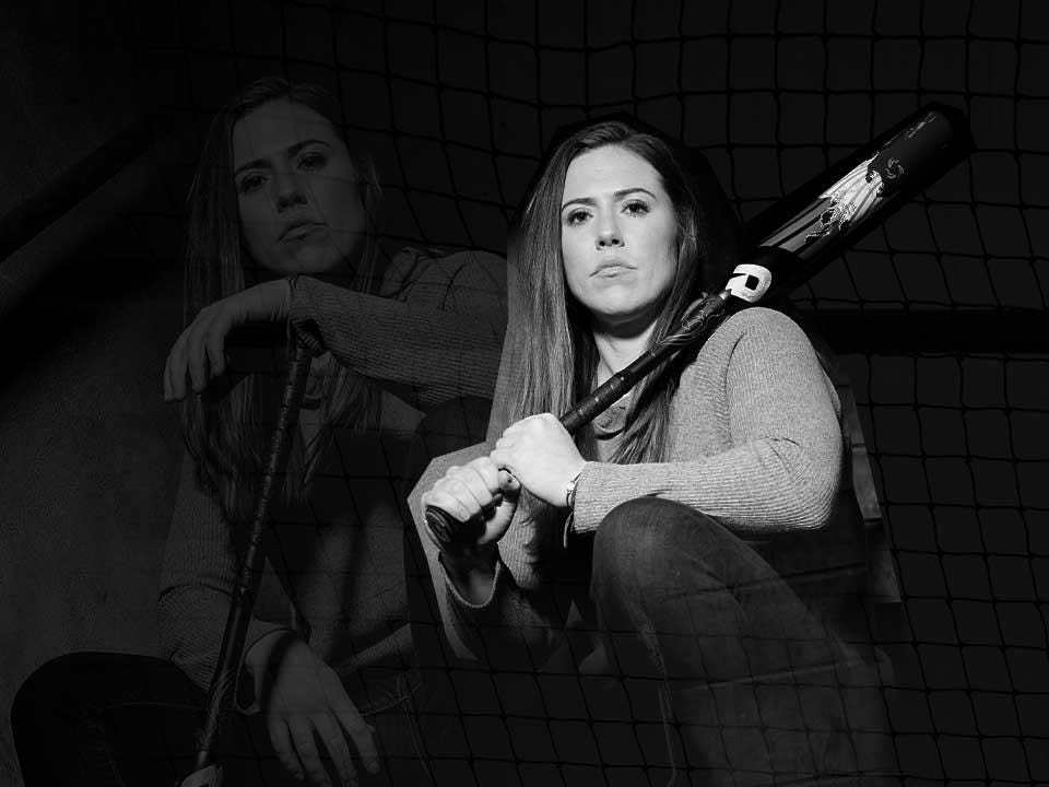 Black and white portrait of Chiddy, crouching down, holding softball bat